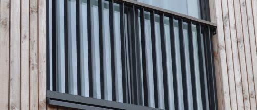 Zwart frans balkonhekwerk met donkerhouten leuning