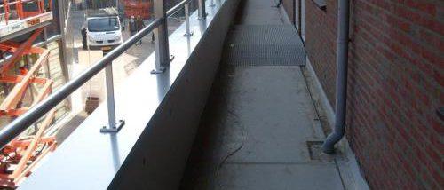 Grijze balkonleuning boven winkelstraat